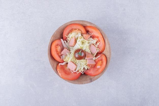 Geriebener käse mit würstchen und tomaten in holzschale.