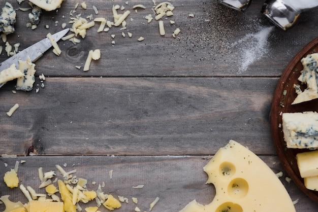 Geriebener käse und scheiben auf grauem hölzernem schreibtisch für das schreiben des textes