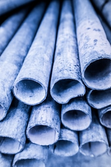 Geringe schärfentiefe des metallrohrstapels im blauton. abgerundete eisenrohrform.