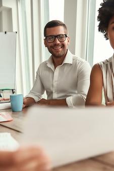 Gerne hier arbeiten. junger und gutaussehender mann mit brille, der eine tasse kaffee hält und mit einem lächeln in die kamera schaut, während er am bürotisch sitzt. geschäftsleute. brainstorming
