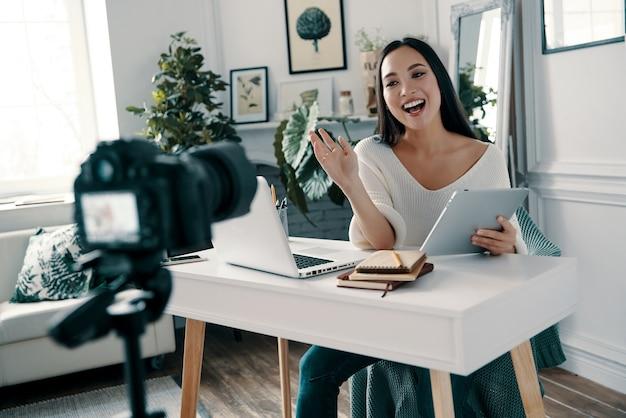Gerne teilt sie ihre ideen. schöne junge frau, die gestikuliert und lächelt, während sie ein neues video für ihren blog dreht