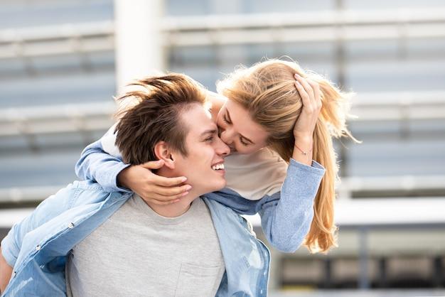 Gerne zeit miteinander zu verbringen. modeporträt des jungen schönen paares im freien. attraktive jungen und mädchen, die sich umarmen und küssen.