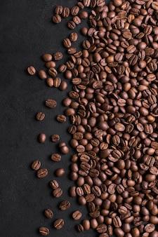 Geröstete bohnen des geschmackvollen kaffees auf schwarzem hintergrund