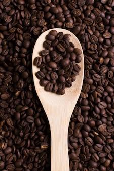 Geröstete bohnen des geschmackvollen kaffees im löffel