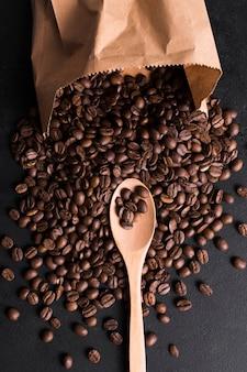 Geröstete bohnen mit geschmackvoller kaffee- und einkaufspapiertüte