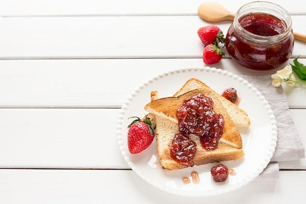 Geröstete brotscheiben mit erdbeermarmelade und einem glas marmelade auf weißem holzhintergrund