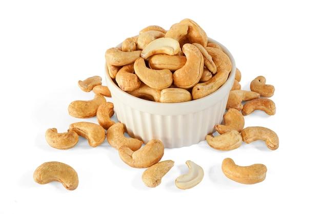 Geröstete cashewnüsse in der weißen schüssel isoliert