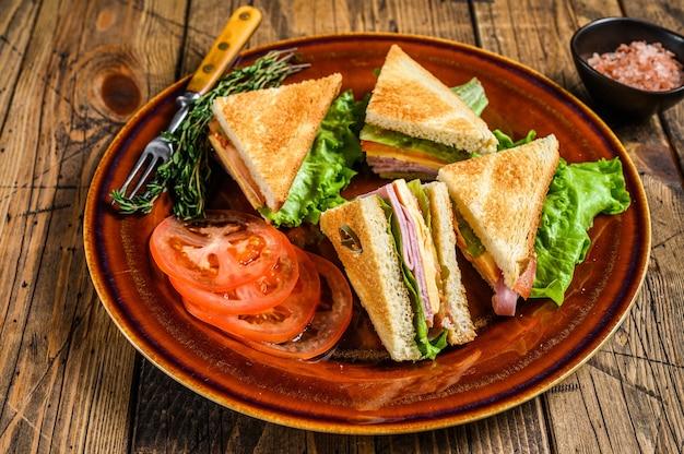 Geröstete club-sandwiches mit schweinefleischschinken, käse, tomaten und salat auf einem teller. holztisch. draufsicht.