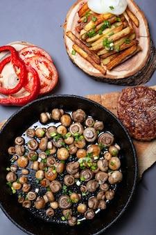 Geröstete goldene champignonpilze mit frühlingszwiebeln in einer gusseisernen pfanne. saftiges schnitzel mit pommes frites und gemüse auf waldholzuntersetzern auf einer grauen hintergrundoberansicht.
