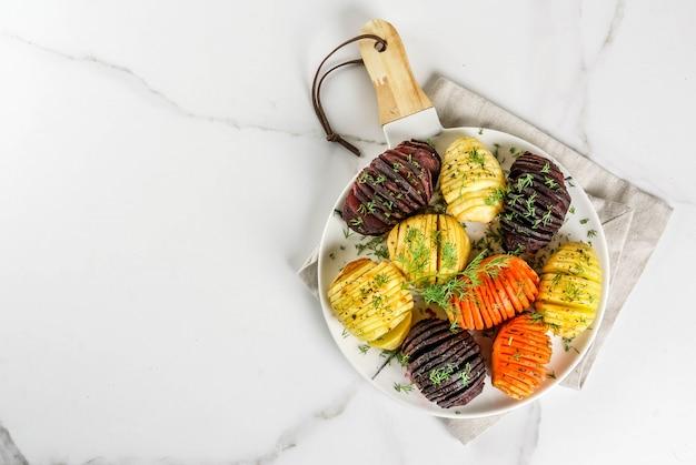 Geröstete hasselback-rüben, karotten, kartoffeln, mit frischen kräutern