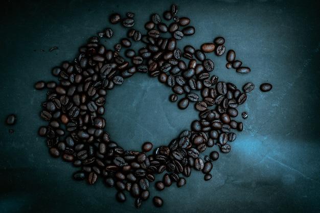 Geröstete kaffeebohnen auf einem dunklen hintergrund.