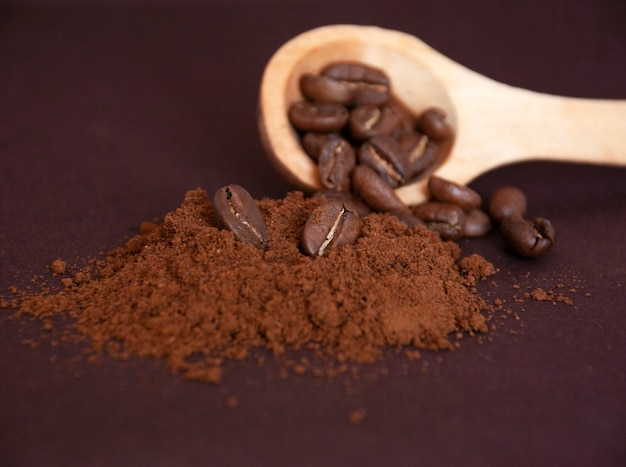 Geröstete kaffeebohnen auf einem haufen gemahlenen kaffees und in einem holzlöffel.