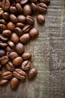 Geröstete kaffeebohnen auf rustikalem hölzernem hintergrund. lebensmittelzutaten, draufsicht