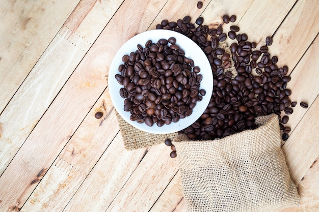 Geröstete kaffeebohnen aus einem sack auf holztischhintergrund gegossen. ansicht von oben