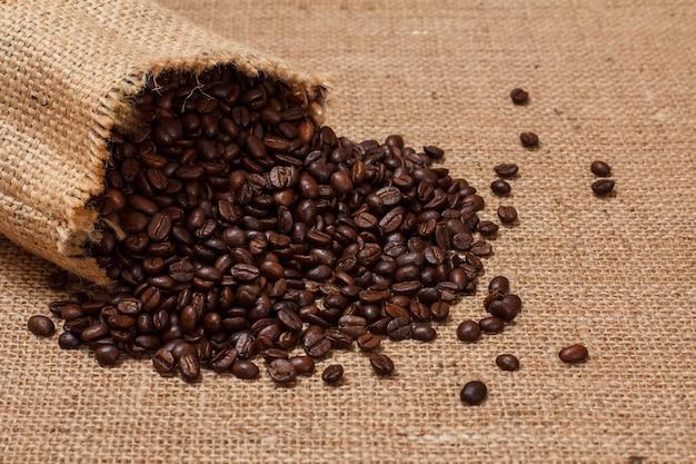 Geröstete kaffeebohnen der nahaufnahme in einem segeltuchsack auf sackleinenhintergrund.