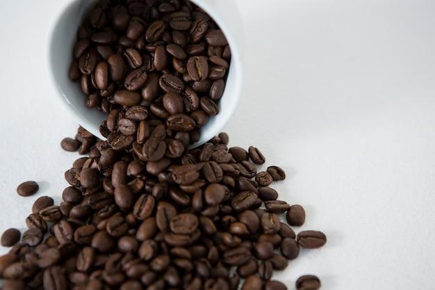 Geröstete kaffeebohnen, die aus der tasse verschüttet werden