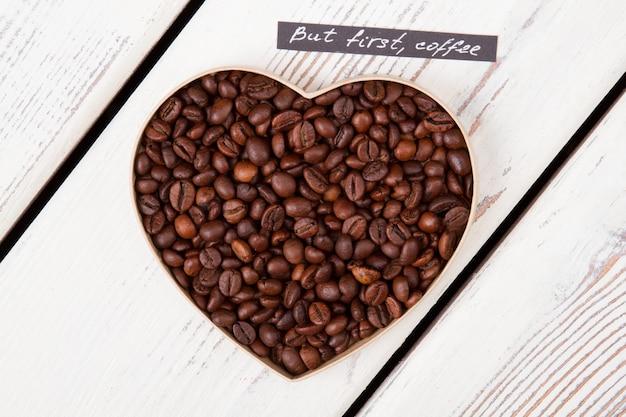 Geröstete kaffeebohnen, die herzform bilden, hautnah. aber zuerst kaffee. draufsicht flach.