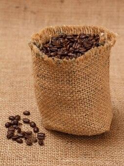 Geröstete kaffeebohnen in einem segeltuchsack auf sackleinenhintergrund.