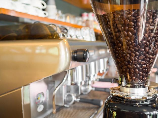 Geröstete kaffeebohnen in einer elektrischen kaffeemühle zum aufbrühen und servieren von kaffee.