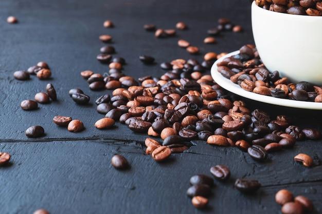 Geröstete kaffeebohnen in einer tasse kaffee
