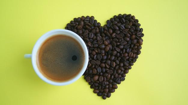 Geröstete kaffeebohnen in form des herzens an der gelben wand neben der tasse kaffee draufsicht