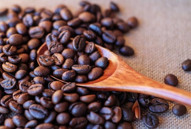 Geröstete kaffeebohnen in holzlöffel auf sackleinen draufsicht