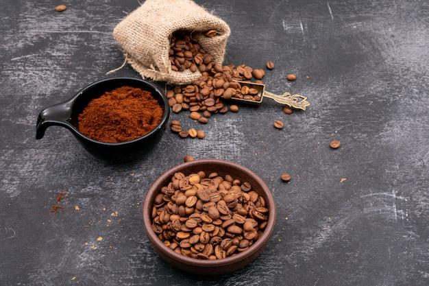 Geröstete kaffeebohnen in keramikschale und sackleinen und kaffeepulver auf dunklen tisch