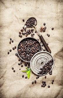 Geröstete kaffeebohnen mit alten werkzeugen. auf textilsack.