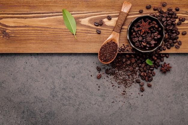 Geröstete kaffeebohnen mit kaffeepulver auf dunklem stein.