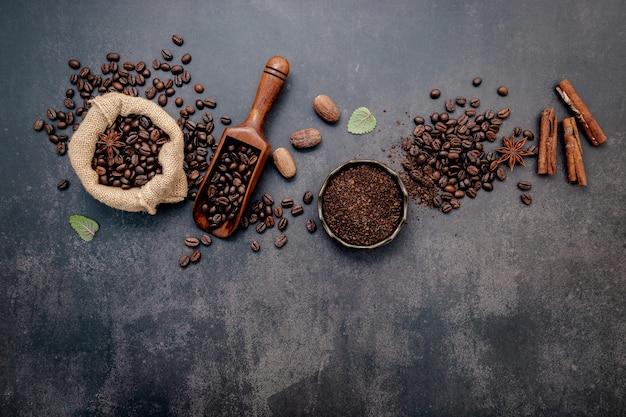 Geröstete kaffeebohnen mit kaffeepulver und geschmackvollen zutaten für eine leckere kaffeezubereitung auf dunklem stein.