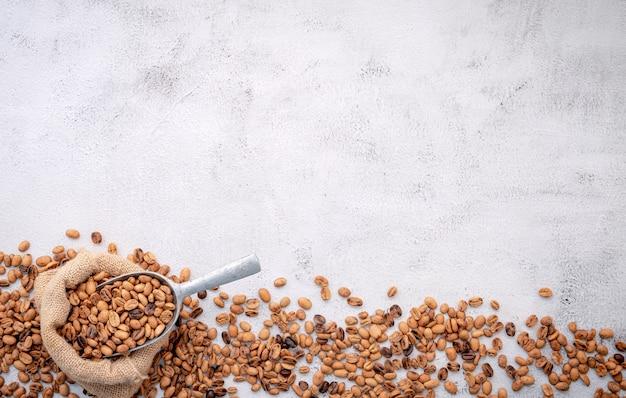 Geröstete kaffeebohnen mit schaufeln auf weißem beton.