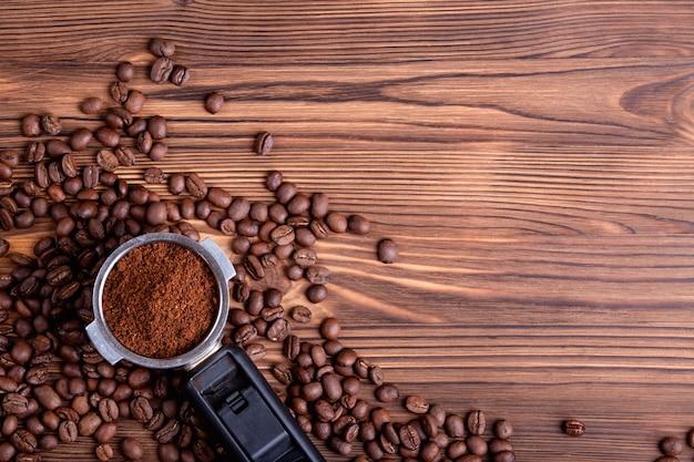 Geröstete kaffeebohnen und ein portafilter mit gemahlenem kaffee auf einem braunen hölzernen hintergrund mit copyspace. flach liegen.