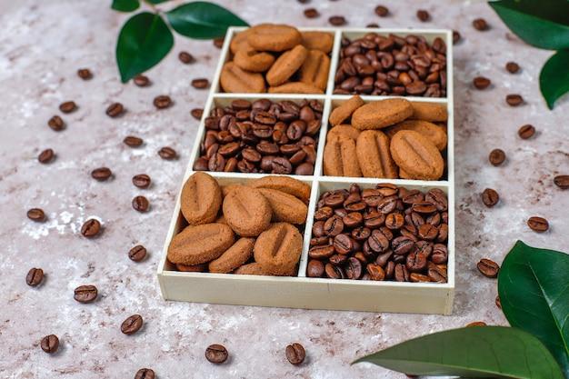 Geröstete kaffeebohnen und kekse in kaffeebohnenform