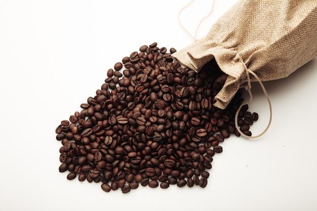 Geröstete kaffeebohnen verstreut aus der tasche isoliert auf weiß