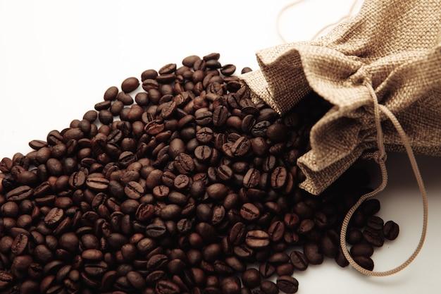 Geröstete kaffeebohnen verstreut von der beutelnahaufnahme.