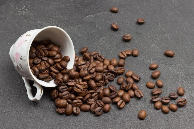 Geröstete kaffeebohnen werden aus der tasse auf den tisch gestreut. schwarzer hintergrund. ansicht von oben