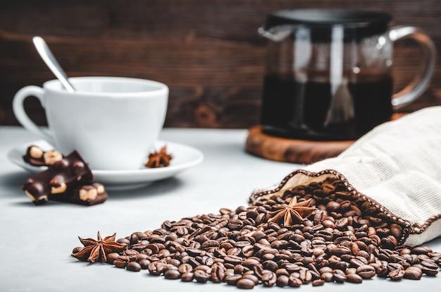 Geröstete kaffeebohnen werden aus einer tüte auf hellem steinhintergrund mit einer tasse und einer glaskaffeekanne verstreut