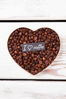 Geröstete kaffeekörner, die herz bilden. kaffeeliebe und romantisches konzept.