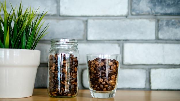 Geröstete kaffeesamen in einer flasche, eine glasflasche arrangieren in einer linie mit kleinen pflanzen