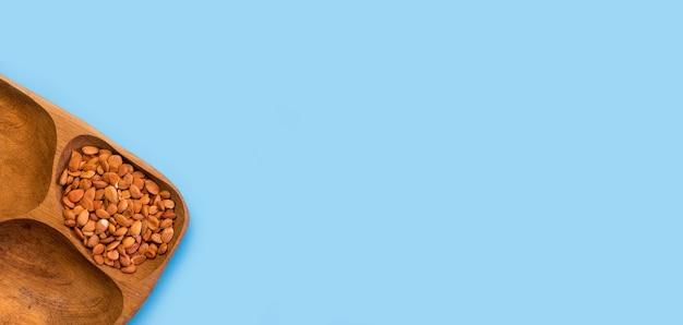 Geröstete mandeln in einem umweltfreundlichen holzbehälter auf blauem grund.