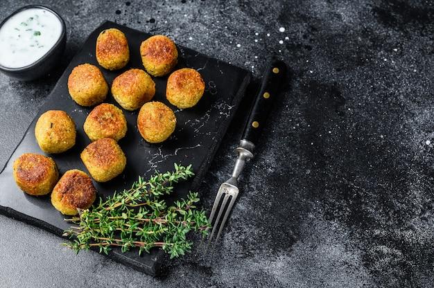 Geröstete vegetarische falafelbällchen aus gewürzten kichererbsen mit knoblauch-joghurt-sauce