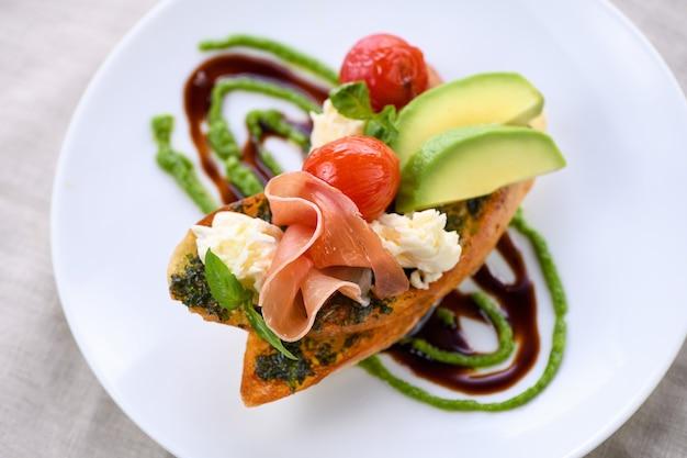 Gerösteter baguette-toast mit pesto-sauce, einer scheibe parmaschinken, mozzarella, tomate und avocado