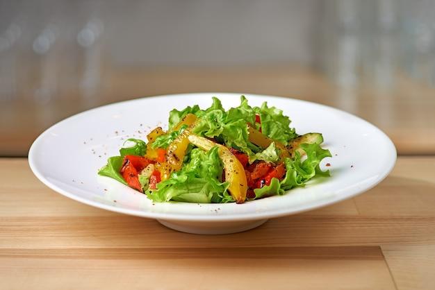 Gerösteter gelber und roter paprikasalat mit kapern und oliven in einer blauen schüssel.