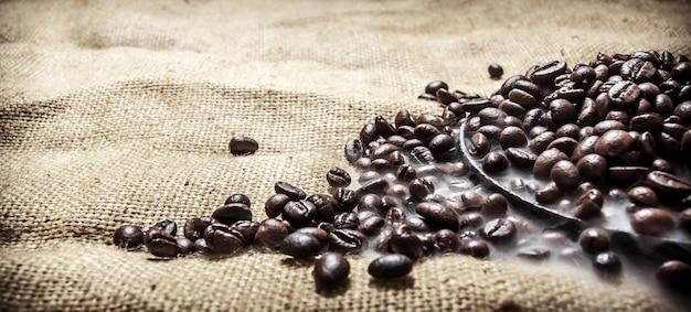 Gerösteter kaffee in der pfanne. auf textilsack.
