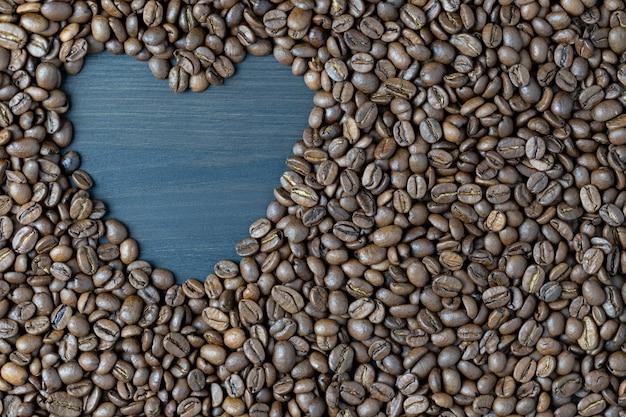 Gerösteter kaffeebohnenhintergrund mit platz für text in form des herzens