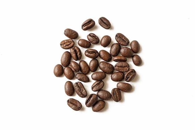 Gerösteter kaffeebohnenstapel lokalisiert auf weißem hintergrund. von oben. geröstete kaffeebohnen nahaufnahme makrofoto