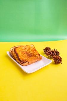 Geröstetes brot auf einem weißen teller mit fichtenblumen auf gelbem und grünem papierhintergrund. toast zum frühstück. vertikales foto
