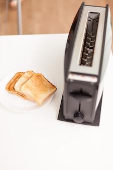 Geröstetes brot in der nähe von elektrischem toaster auf dem tisch in der küche.