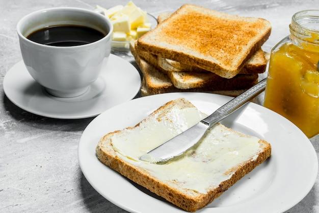 Geröstetes brot mit butter und heißem kaffee. auf einer rustikalen oberfläche.