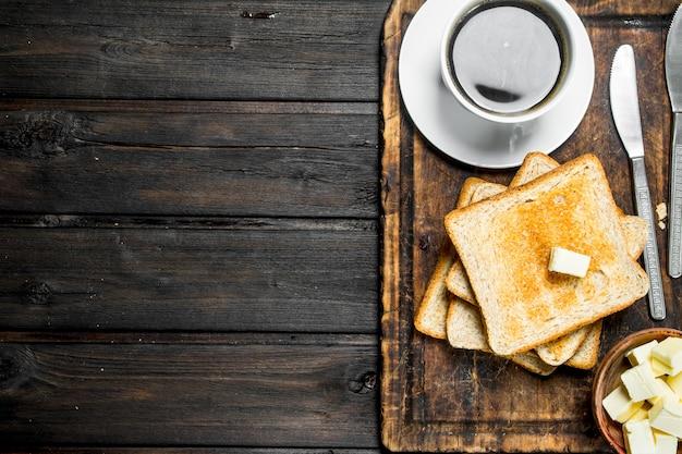 Geröstetes brot mit butter und kaffee. auf einem holz.